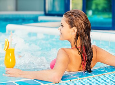 Girl Relaxing & Enjoying a Drink at In Ground Outdoor Pool